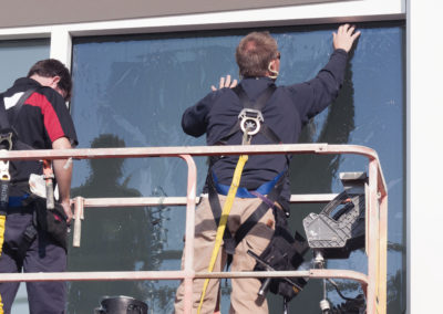 Sunshine Control employees apply tint to the exterior windows of an office building.