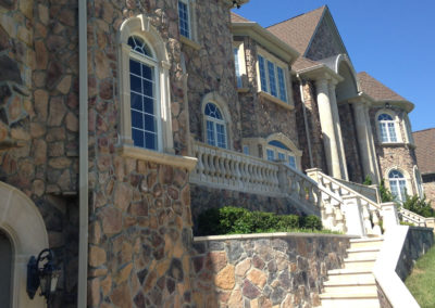 Exterior of large residential building with rock walls and windows tinted by Sunshine Control
